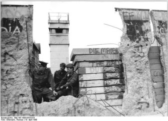 East German soldiers peering through a hole in the Berlin Wall. April 1990.